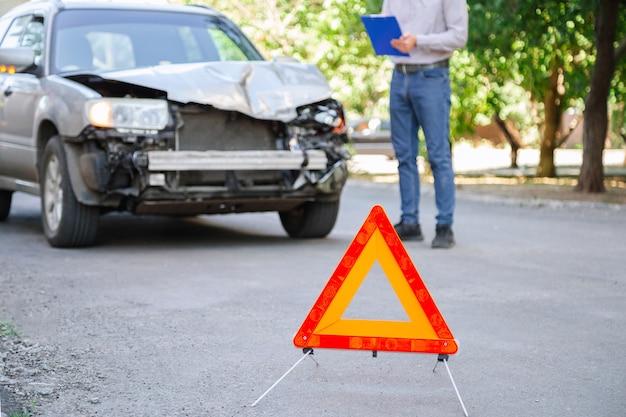 男性保険代理店は、自動車事故後の難破した車での保険事故について説明しています。道路上の自動車保険。事故後に読書をしているタブレットを持つ男。道路上の壊れた車。