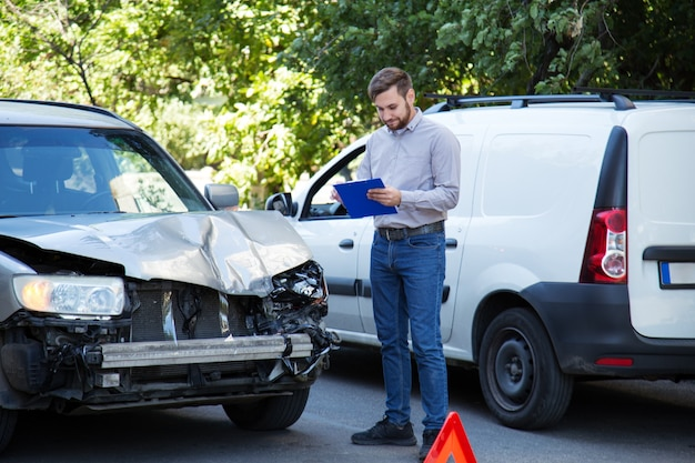 Man insurance agent with auto insurance blank against destroyed car in car crash traffic accident on road. smashed broken front auto headlight on car accident. auto life and health insurance.