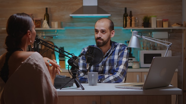 Uomo che intervista il vlogger della donna in studio domestico per il podcast. spettacolo online creativo produzione in onda trasmissione su internet host in streaming di contenuti live, registrazione di comunicazioni sui social media digitali