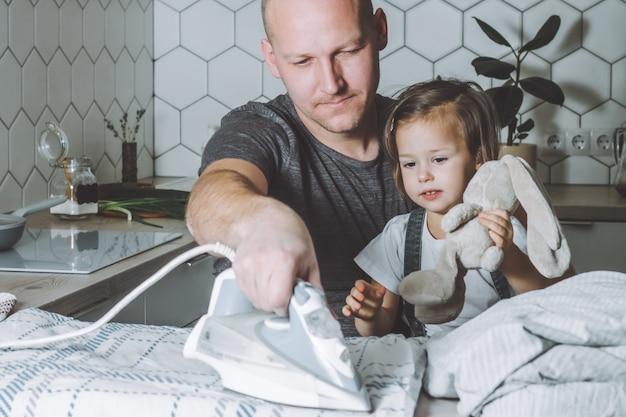 Мужчина гладит постельное белье с маленькой дочкой на коленях, отец занимается домашними делами