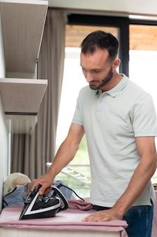 家で乾かした後、衣類にアイロンをかける男