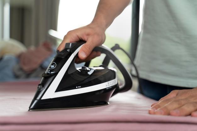 Мужчина гладит одежду после сушки дома