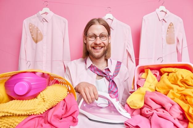 洗濯室で服をアイロンがけをする男性は、陽気な使い方をするエレクトリス ストリーム アイロンは丸い眼鏡のシャツを着て、ピンクに分離された首にネクタイを付けた