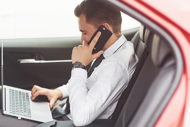 Man - это мужчина, работающий на ноутбуке и тестирующий на мобильных устройствах.