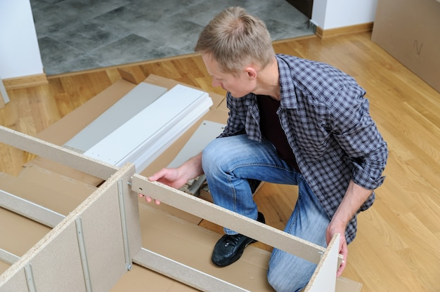 The man is assembling furniture from chipboard boards