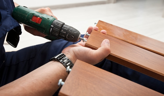 The man is assembling wooden furniture in home