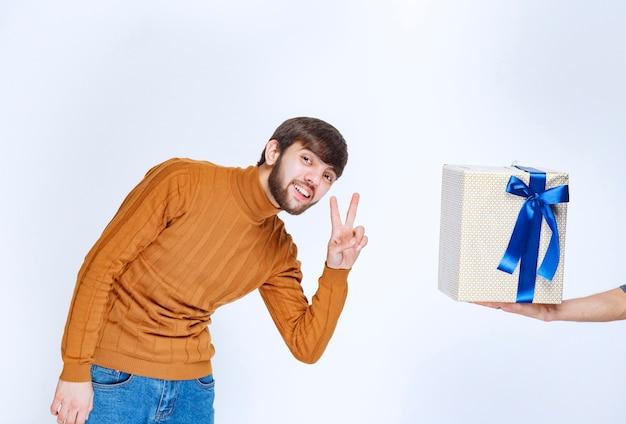 男は青いリボンが付いた白いギフトボックスを提供されており、彼はそれを楽しんでいます。