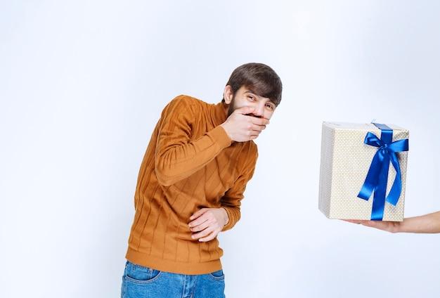 男は青いリボンが付いた白いギフトボックスを提供されており、彼はそれを笑っています。