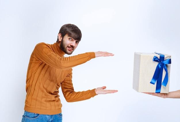 男は青いリボンが付いた白いギフトボックスを提供されており、彼はそれを両手で取っています。