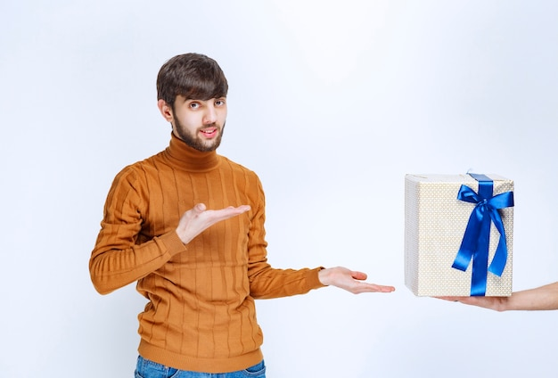 Man is being offered a white gift box with blue ribbon and he is pointing at it.