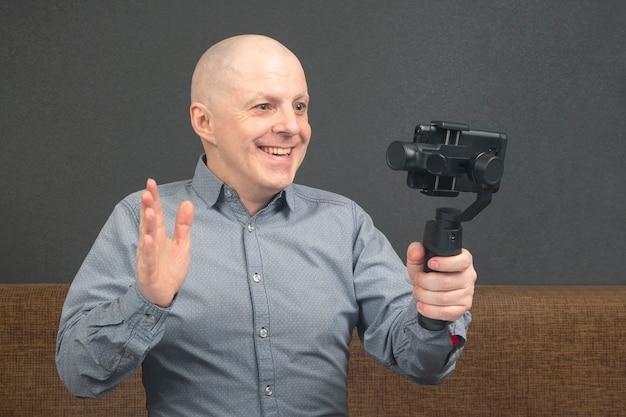 男はスタビライザー付きのスマートフォンにホームビデオを放送しています