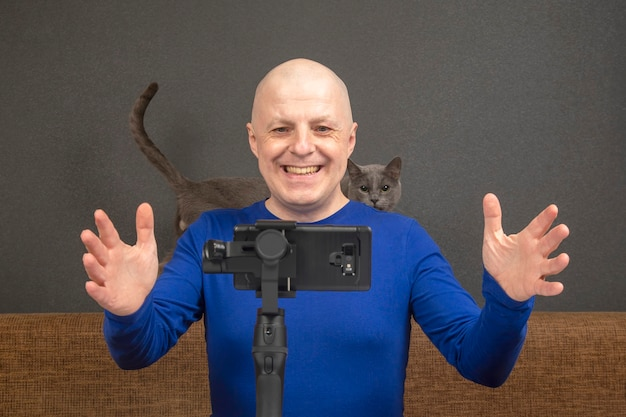 Man is broadcasting a home video to a smartphone with a stabilizer