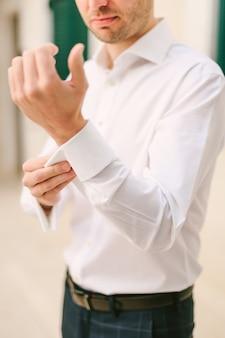 Мужчина застегивает манжеты белой рубашки на фоне стены крупным планом