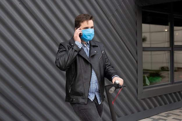 男は電動スクーターに医療マスクを身に着けている携帯電話で呼び出す
