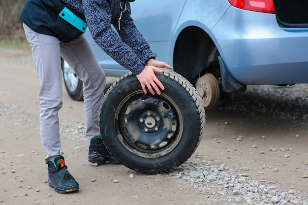 Man is changing tire with wheel on the car