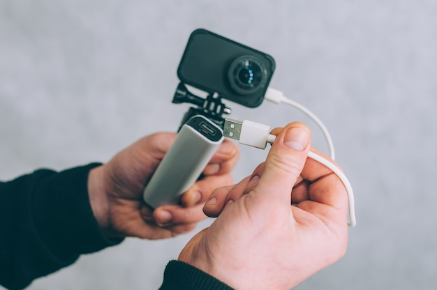 A man is charging an action camera with a portable charger.