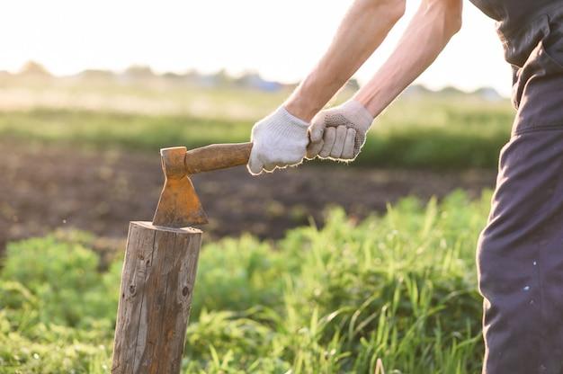 男はヴィンテージの斧で木を切り刻んでいます。