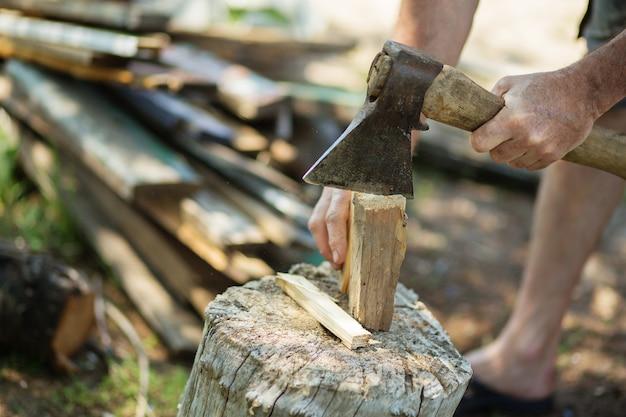 Человек рубит дрова старинным топором