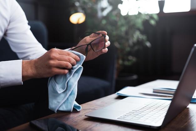 Мужчина чистит очки синей тканевой салфеткой
