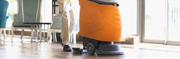 Мужчина убирает вестибюль отеля промышленным пылесосом