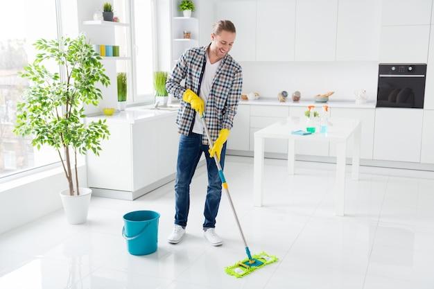 男はモダンなキッチンを掃除しています