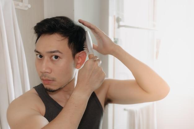 男はバスルームで髪をとかしている