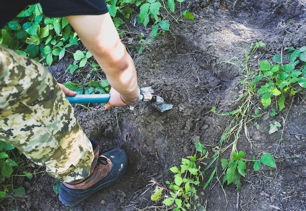남자는 삽으로 땅을 파고 있다. 자연에서 관광입니다. 야외 계단 만들기.