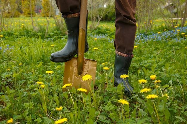남자는 스 페이딩 포크로 봄 토양을 파고 있습니다.