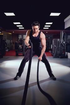 男はジムでロープを使って運動をしている