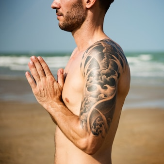 A man is doing a yoga at the beach