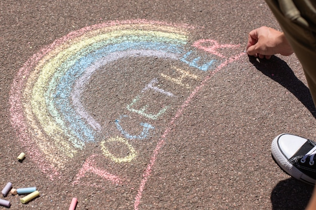 男はlgbtの虹のシンボルを描いています