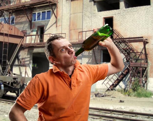 Мужчина пьет алкоголь в трущобах