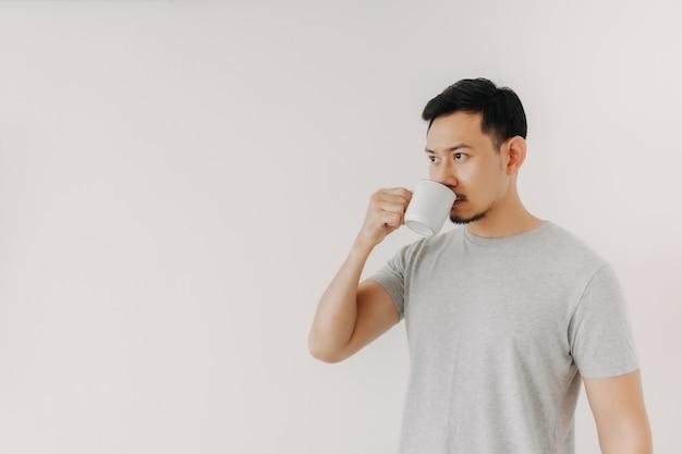 男は白い背景で隔離のコーヒーやお茶を飲んでいます