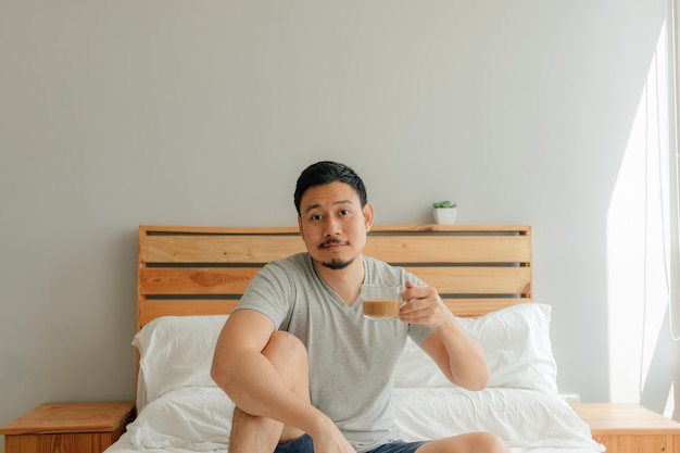 Man is drinking a cup of coffee on the bed in his bedroom.