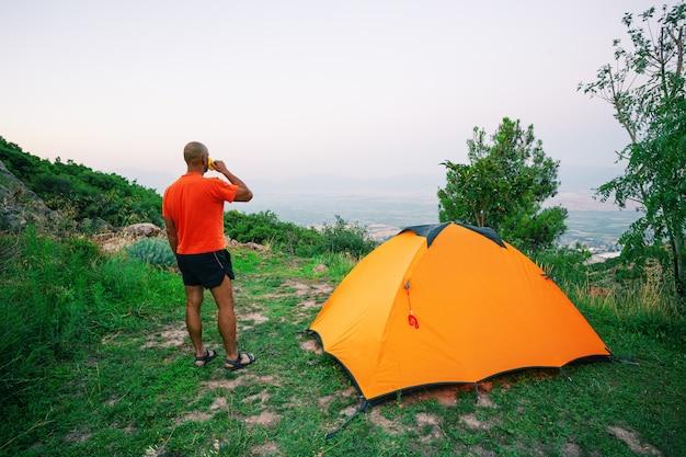 Мужчина пьет из чашки возле оранжевой палатки, стоящей на холме
