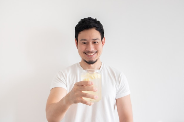 男は、分離した白い背景でアイスレモンソーダを飲んでいます。