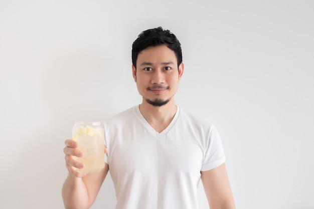 男は分離した白い背景でアイスレモンソーダを飲んでいます