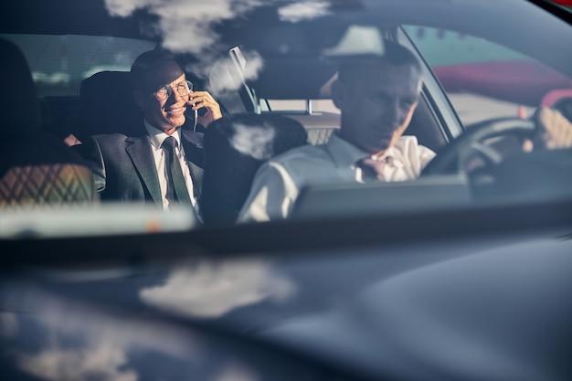 Мужчина ведет комфортабельную машину, а его босс говорит по мобильному телефону сзади