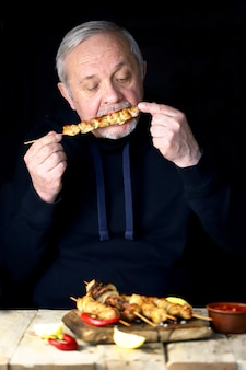 The man is eating a chicken skewer