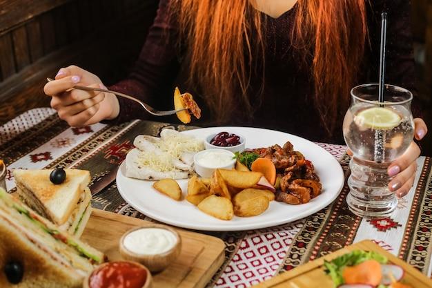 Мужчина ест жареный картофель с курицей и овощами