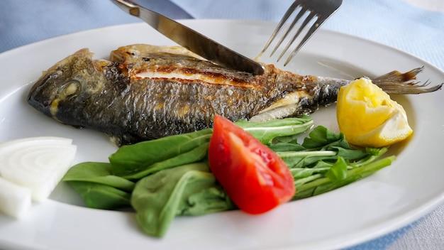 남자는 레스토랑 접시 클로즈업에서 포크와 나이프로 생선 튀김을 먹고 있다