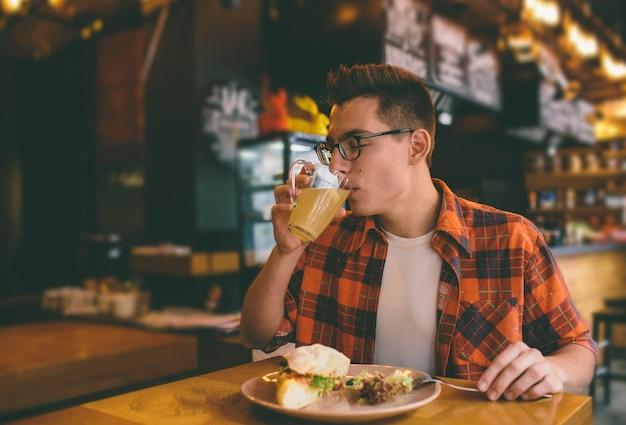 남자는 식당에서 먹고 맛있는 음식을 즐기고 있습니다.