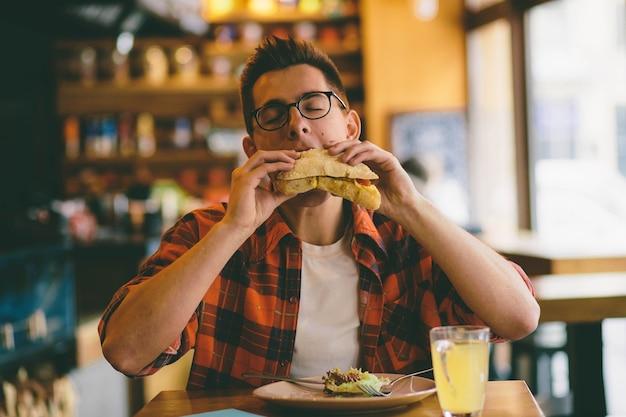 남자는 식당에서 먹고 맛있는 음식을 즐기고 있습니다. 프리미엄 사진