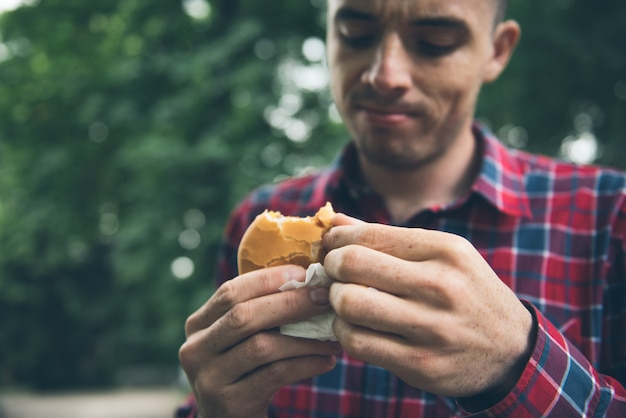 Man is eating in the park and enjoying delicious food