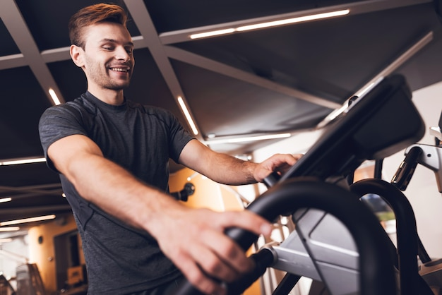 A man is engaged in an elliptical trainer