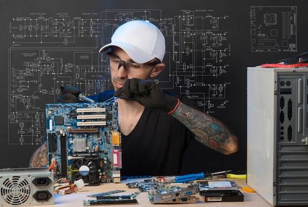 Man is engaged in repair of computers