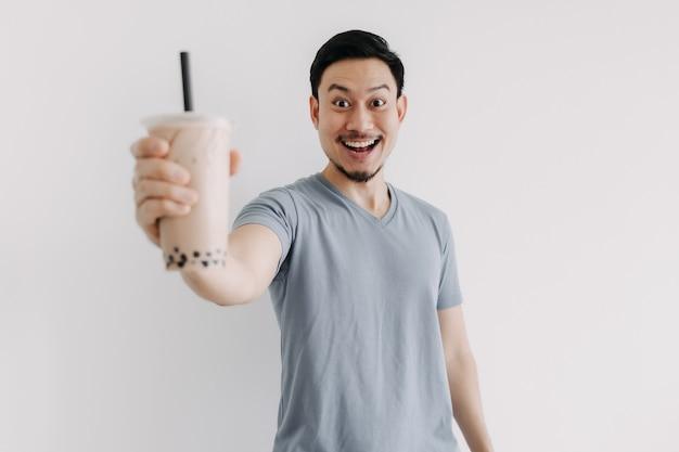 男は白い背景で隔離の彼のボバ茶に満足している