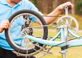Man is fixing bicycle. Photo is focused at a wheel.