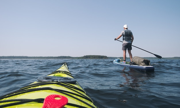 A man is floating on a paddle board. view from the kayak.