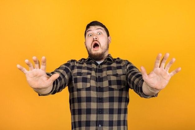 The man is frightened repelled by the viewer  in a state of shock, the image on an orange wall